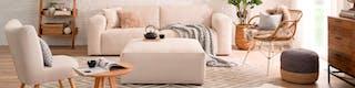 Pastellfarbenes Wohnzimmer mit Zweier-Sofa, Beistellhocker, Korbsessel und bezogener Stuhl für zahlreiche Sitzmöglichkeiten