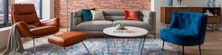 Graues Sofa, cognacfarbener Sessel mit Fußbank, blauer Samtsessel und Couchtisch auf buntem Teppich stehend