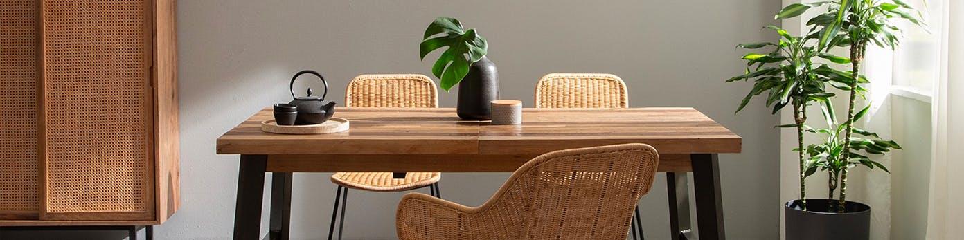 Massiver Holztisch, an dem Korbstühle stehen, dahinter ein Schrank mit heller Front aus Geflecht und Pflanzen daneben