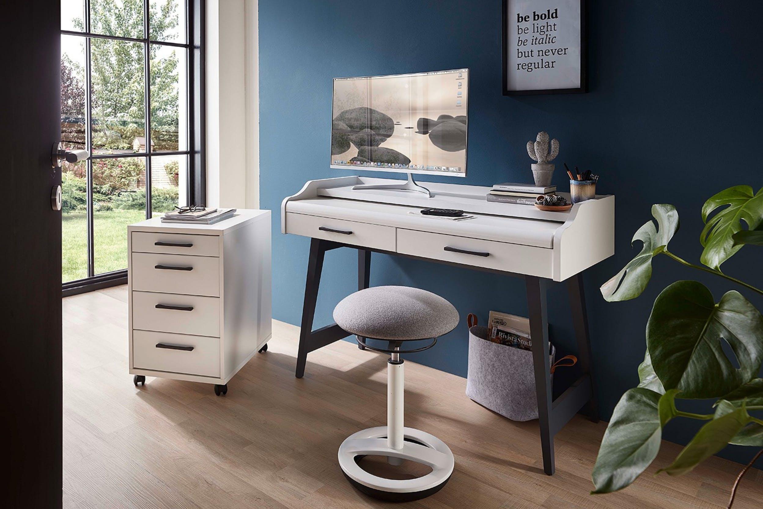 Schmaler Schreibtisch vor dunkelblauer Wand umrandet von Rollcontainer, Bildern und Pflanzen