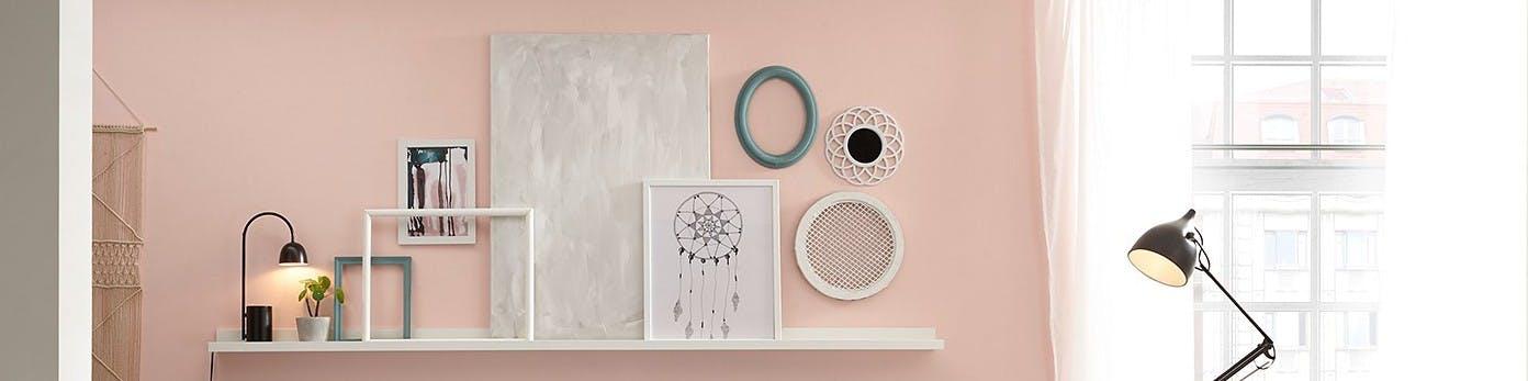 Lässig aufgestellte Bilder und Kunstwerke an rosa gestrochener Wand