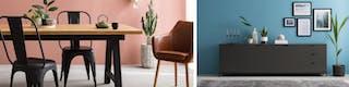 Schwarze Stühle aus Metall und lederbezogener Sessel an Holztisch vor altrosa gestrichener Wand sowie anthrazitfarbenes Sideboard vor blauer Wand