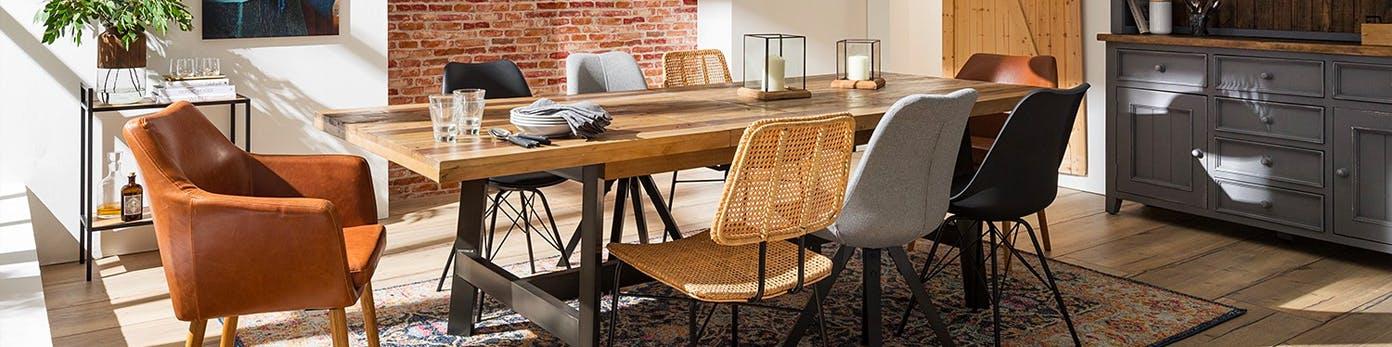 Langer Massivholztisch, an dem unterschiedliche Esszimmerstühle aus Leder, Kunststoff und Korbgeflecht stehen