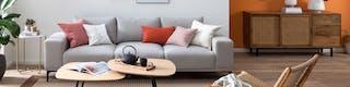 Wohnzimmer mit hellgrauem Sofa, bunten Kissen und Rattanmöbeln