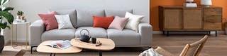 Salon composé d'un canapé gris clair avec des coussins dans les nuances de rose et de rouge et de meubles en bois