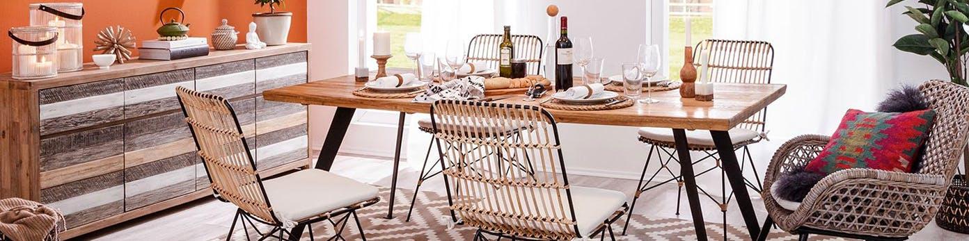Gedeckter Esszimmertisch mit Massivholzplatte sowie Esszimmerstühle mit Sitzkissen und praktisches Sideboard an der Wand zur Aufbewahrung