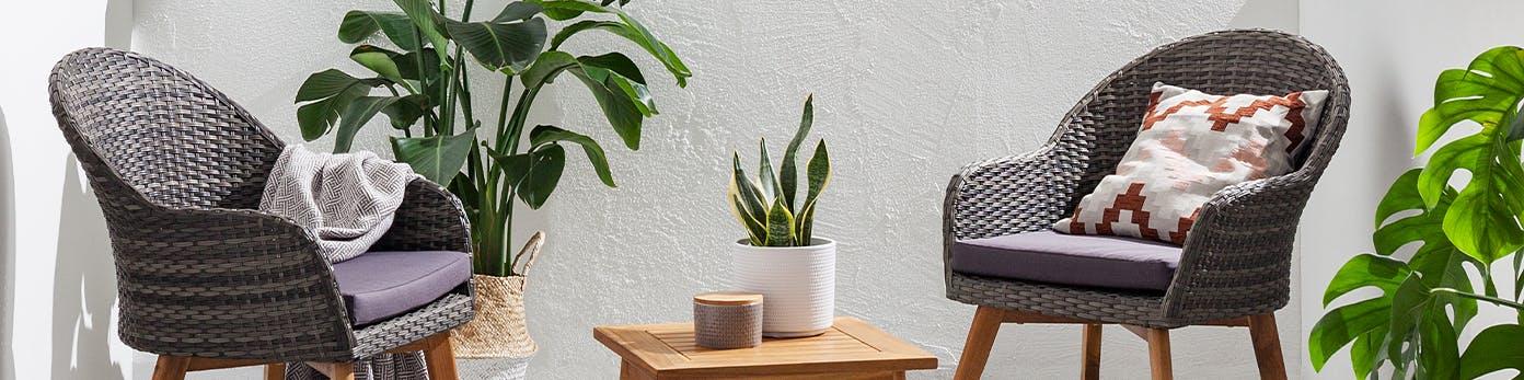 Balkonsessel aus witterungsbeständigem Polyrattan mit gemütlichen Kissen und Pflanzen