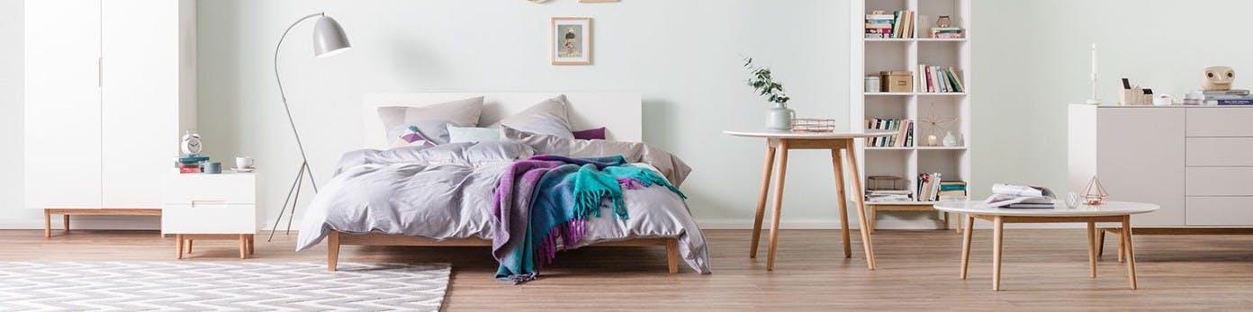 Niedriges Futonbett mit kurzen Holzbeinen und weißen Gestell mit grauer Bettwäsche sowie Stehlampe, Kommode, Schrank, Wandregal mit Büchern und Tische vor hellgrüner Wand