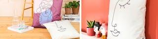 Kissen mit künstlerischem Print auf Untergrund aus Holz und vor roter Wand sorgen für wohnliches Ambiente