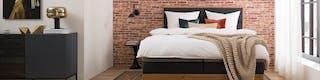 Eingerichtetes Schlafzimmer mit Bett und gemütlichen Bettwaren