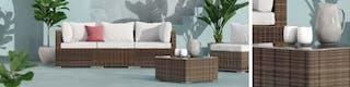 Gartencouch, Beistelltisch und Sessel aus Polyrattan vor türkisem Hintergrund mit großblättrigen Pflanzen