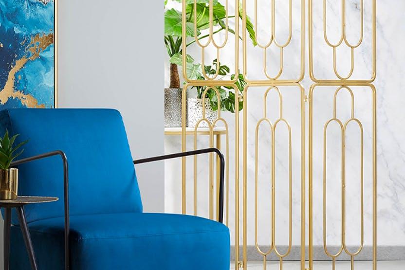 Blauer Sessel vor transparentem Paravent als Raumteiler