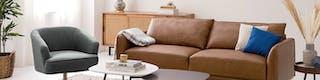 Wohnzimmer mit braunem Sofa Garapu aus Echtleder mit Kissen und Decke sowie grauer Sessel, ineinander verschachtelte Beistelltische, Sideboard mit Wiener Geflecht und Pflanzen