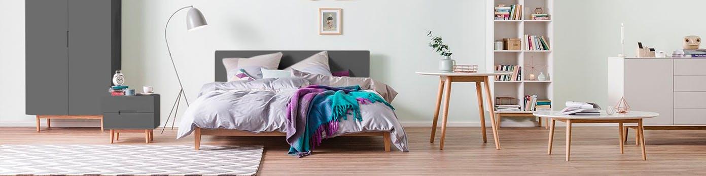 Aufgeräumtes Schlafzimmer mit Stauraum in Schränken und weißem Regal sowie Beistelltische in unterschiedlicher Höhe