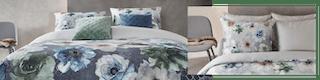 Bett vor grau gestrichener Wand mit geblümter Bettwäsche