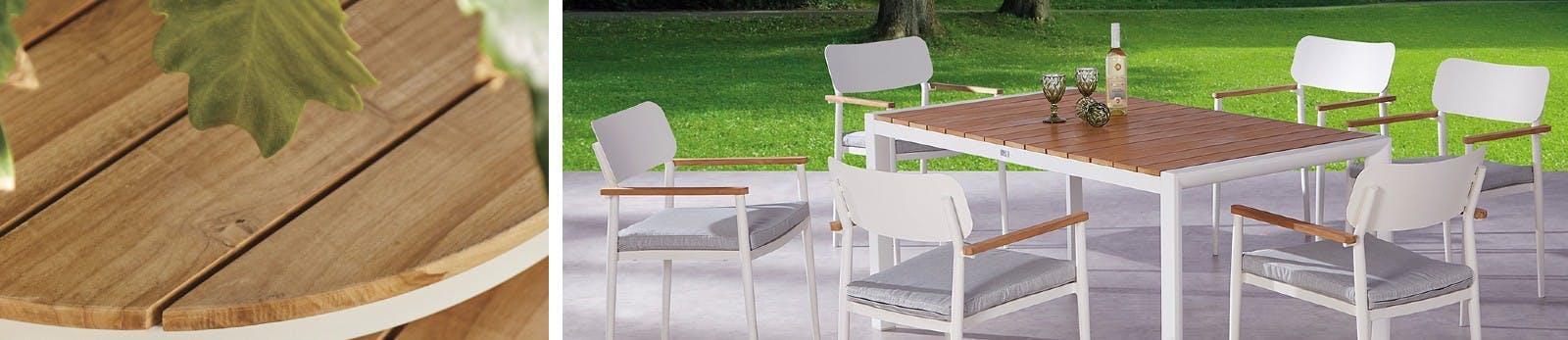 Nahaufnahme von Gartentisch aus Teakholz sowie Holztisch mit weiß lackierten Beinen und sechs darum platzierte Stühle