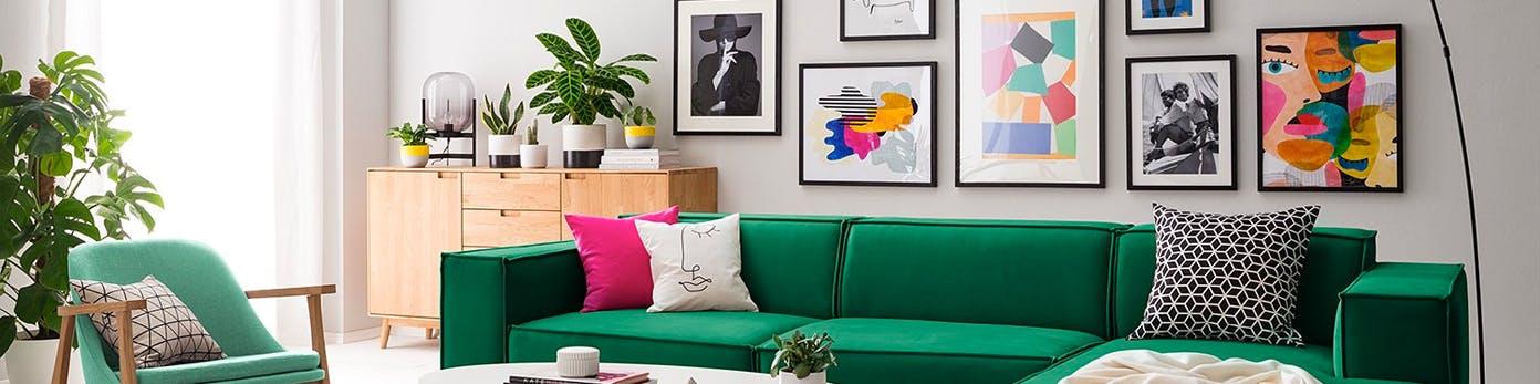 Wohnbereich mit grüner Couch, Sideboard aus hellem Holz mit darauf stehenden Pflanzen und Bildergalerie an der Wand