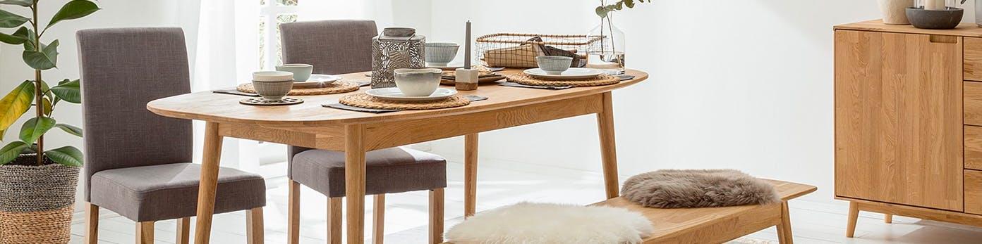Holztisch mit Geschirr und zwei bezogenen Esszimmerstühlen sowie einer Sitzbank, auf der kuschelige Felle liegen