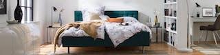 Schlafbereich mit grünem Polsterbett und kuscheliger Bettwäsche separiert vom Arbeitsplatz durch weißes, in den Raum ragendes Regal