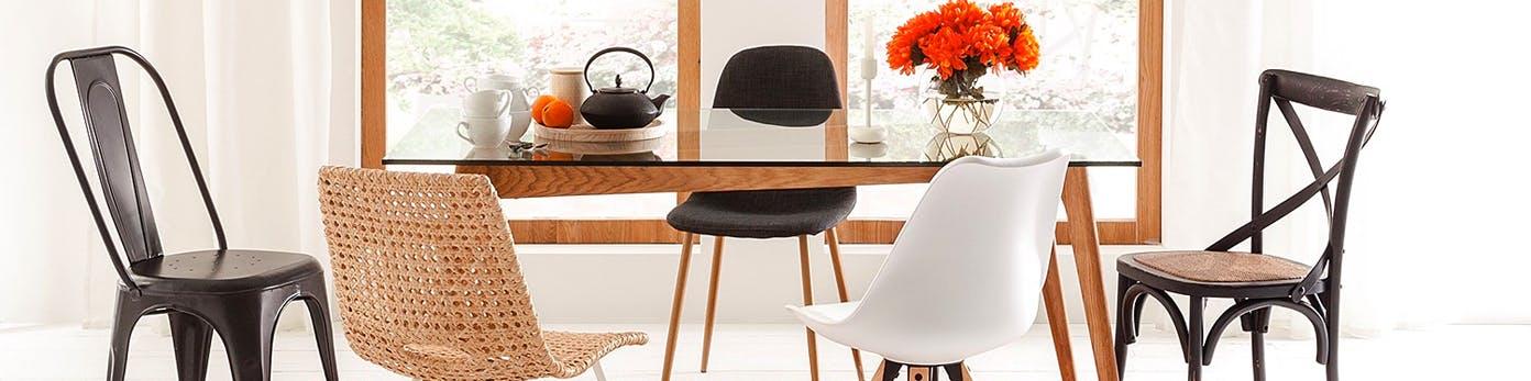 Verschiedene Esszimmerstühle gemixt am Esstisch mit Glasplatte stehend