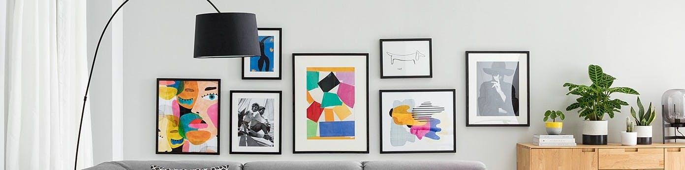 Bunte Bildersammlung an grauer Wand hinter grauem Sofa aufgehängt