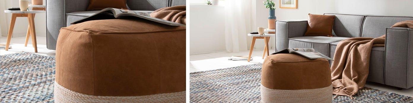 Vielseitig einsetzbarer Polsterhocker auf Teppich stehend mit grauer Couch im Hintergrund und Kissen und Decken in gedeckten Naturtönen
