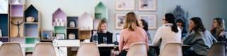 Mitarbeiterinnen an langem Konferenztisch in einem Meeting