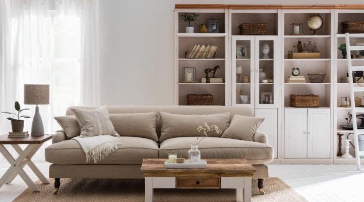 Wohnzimmer im Landhaus Stil mit einem Holzregal von home24 im Hintergrund