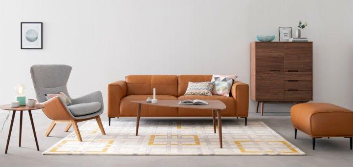 Gemütliche Wohnzimmer mit Leder-Sofa, Sessel und Holz-Kommode im Skandi-Stil - home24