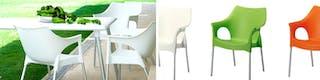 Weißer Gartentisch sowie Gartenstühle in weiß, grün und rot aus Kunststoff