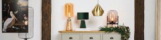 Kommode mit einer goldgelben Tischleuchte aus Glas, einer Tischleuchte aus grünem Samt, einer Pendellampe aus Messing sowie einer Tischleuchte mit schwarzem Rahmen und rauchfarbener Glaskugel. Daneben eine Stehlampe im Industrial-Stil aus schwarzem Metallgeflecht.