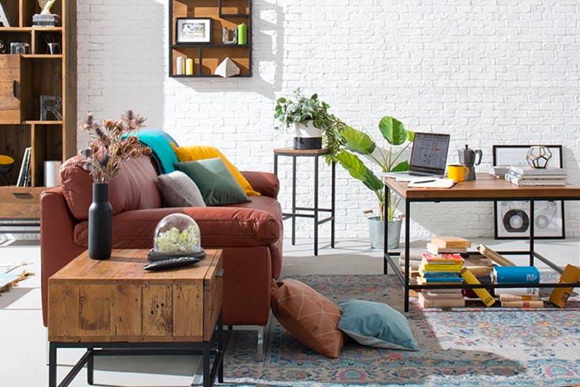 Sofa ragt mittig in den Raum hinein und teilt Wohnzimmer in zwei Bereiche