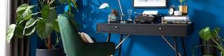 Arbeitsplatz bestehend aus grünem Stuhl und schwarzem, schmalen Tisch mit zwei Schubladen vor blau gestrichener Wand und Grünpflanzen