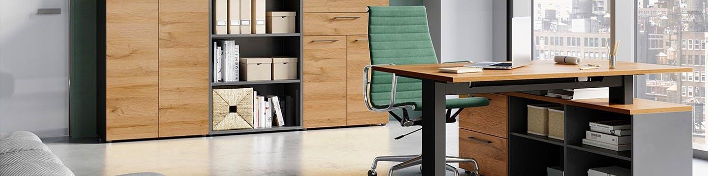 Grüner Bürostuhl hinter höhenverstellbarem Arbeitstisch vor Schränken mit Holzfront und Regal, in dem Aktenordner stehen