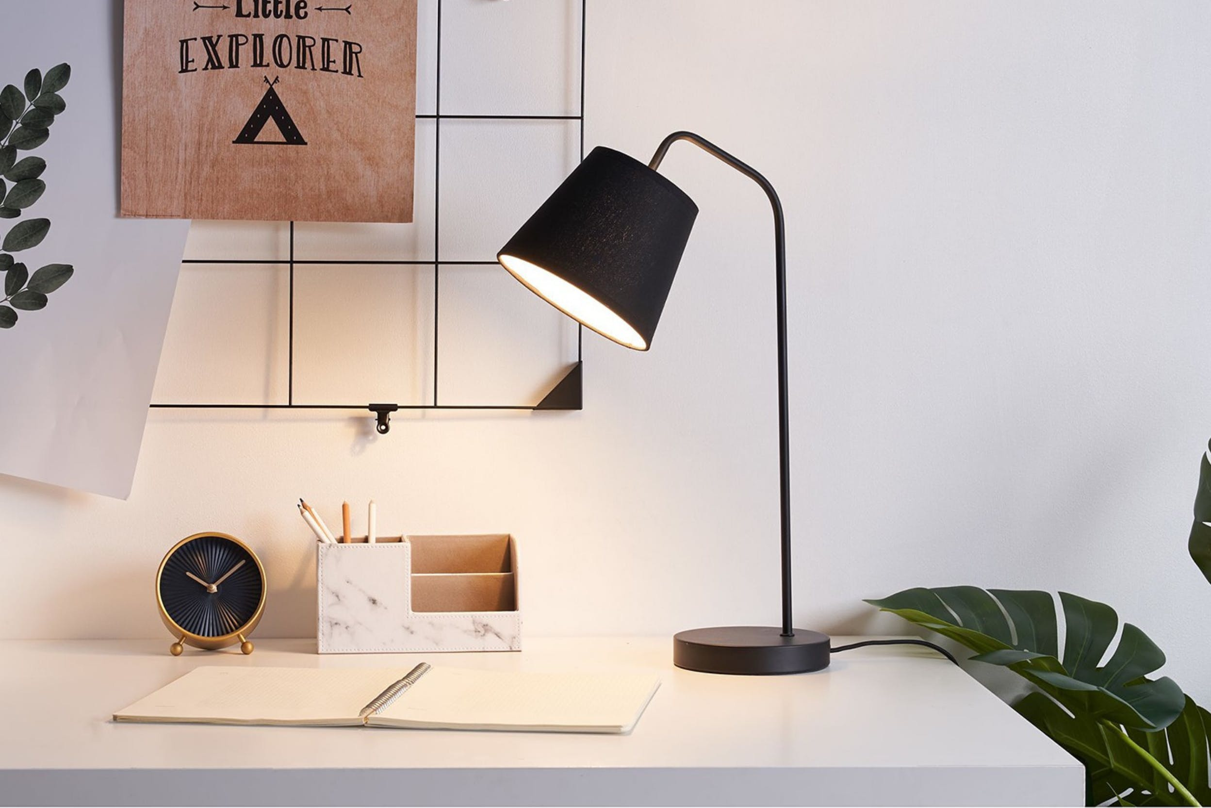 Schwarze Tischlampe auf weißem Schreibtisch