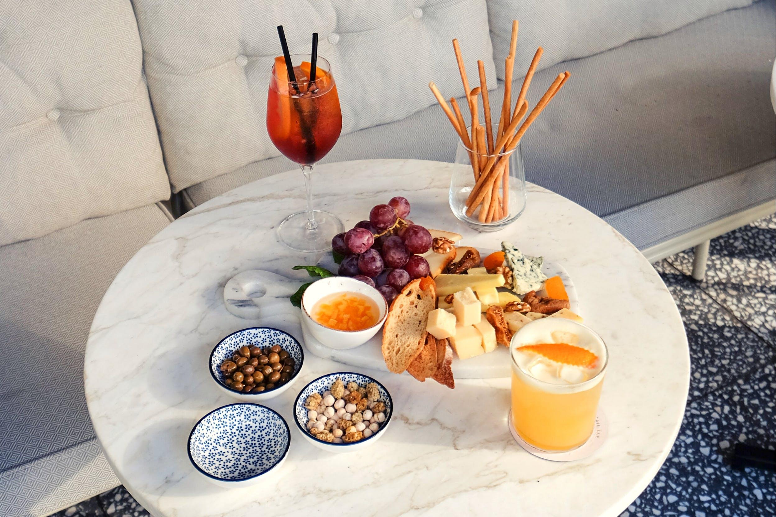 Weißer Tisch mit bunten Schalen, Trauben und Käseplatte