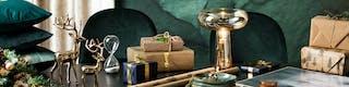 Tisch mit schönen Weihnachtsgeschenken wie einer Tischleuchte aus Glas, goldenen Dekofiguren, Schalen, Kissen und Duftkerzen.