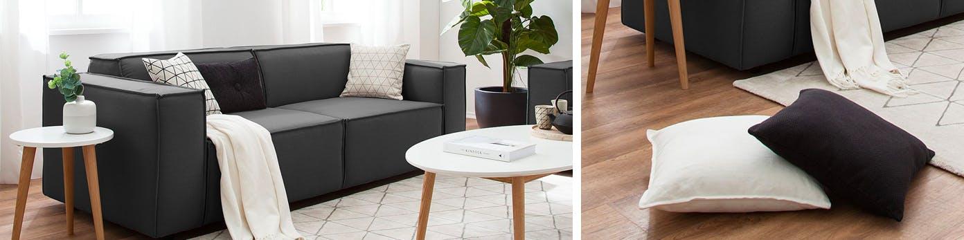 Schwarzes Sofa und darauf liegende helle Kissen mit Rauten-Muster für den Schwarz-Weiß-Look