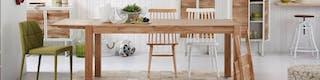 Langer Holztisch, an dem verschiedene Esszimmerstühle stehen sowie Schränke im Hintergrund