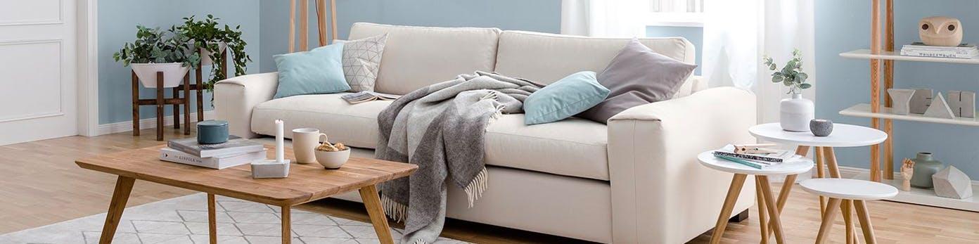 Hell wirkendes Wohnzimmer in Pastellblau gestrichen mit weißer Couch und pastellfarbenen Kissen sowie schlanke Beistelltische und Pflanzenkübel