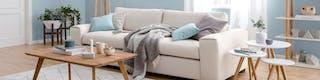 Helles Sofa mit gemütlichen Decken sowie Beistelltische und Wandregal an blau gestrichener Wand sowie Couchtisch aus Holz im Vordergrund