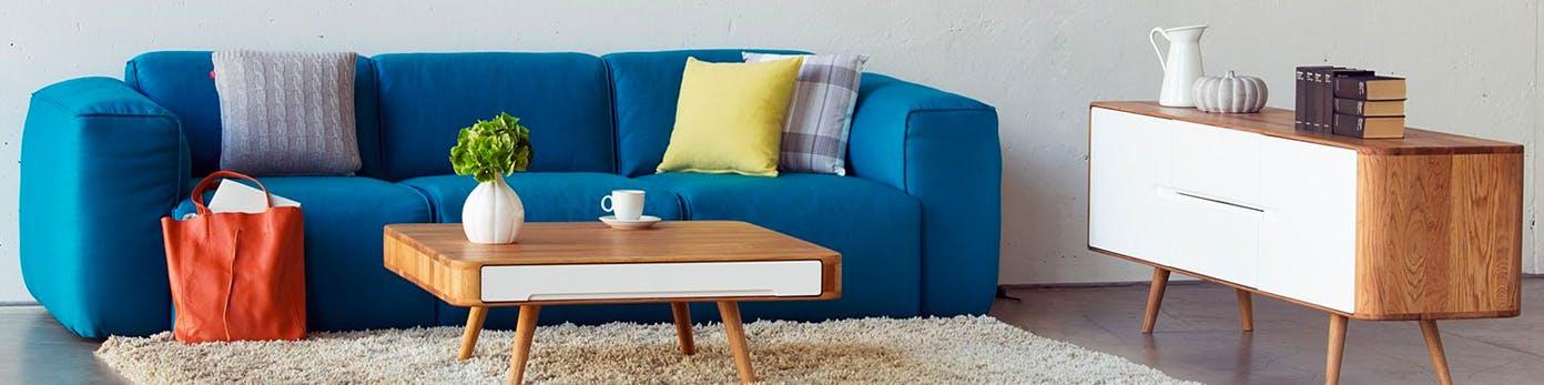 Blaues Sofa kombiniert mit Couchtisch und Sideboard in neutralem Holzfarben