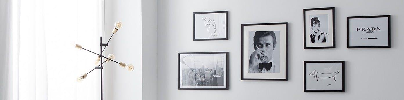 Bilderreihe in Schwarzweiß in schwarzen Rahmen in unterschiedlichen Formaten an grauer Wand platziert