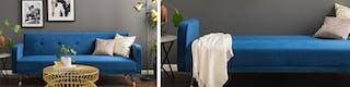 Filigraner Beistelltisch in Gold steht mit blauem, ausklappbaren Schlafsofa vor grauer Wand mit Bildern