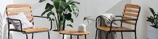 Kleine Sitzecke mit Balkonstühlen, Beistelltisch und Dekor ergänzt durch Pflanzen