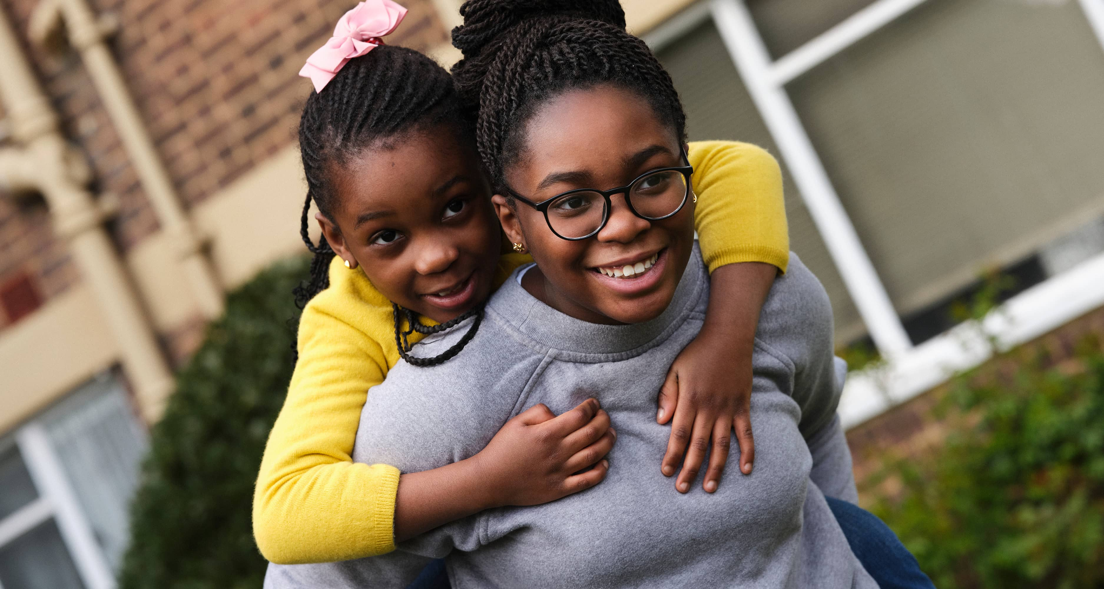 Two girls playing together and smiling outside