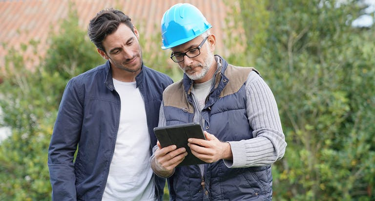 Two men review information on a tablet
