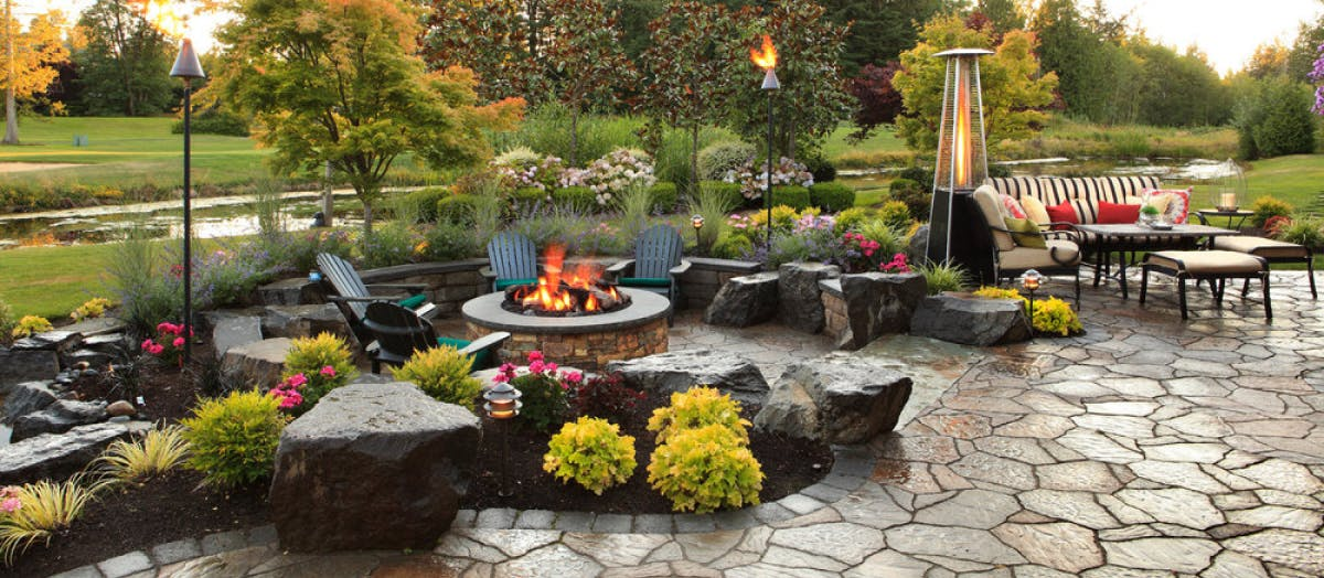 Outdoor patio with a fire pit in a garden.
