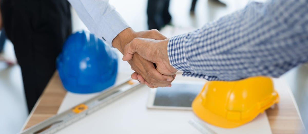 A newly hired pro shakes hands with their new client.
