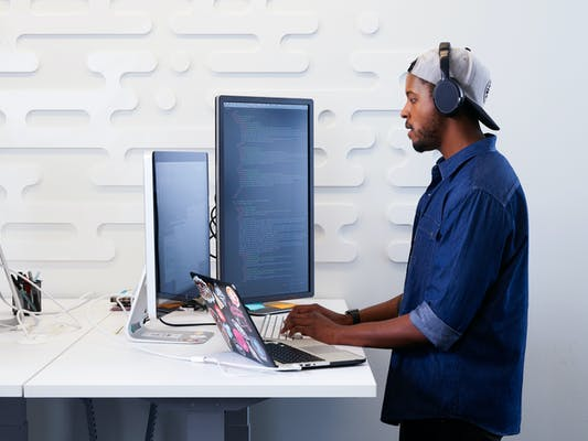 A young man uses a standing desk to do work on his laptop